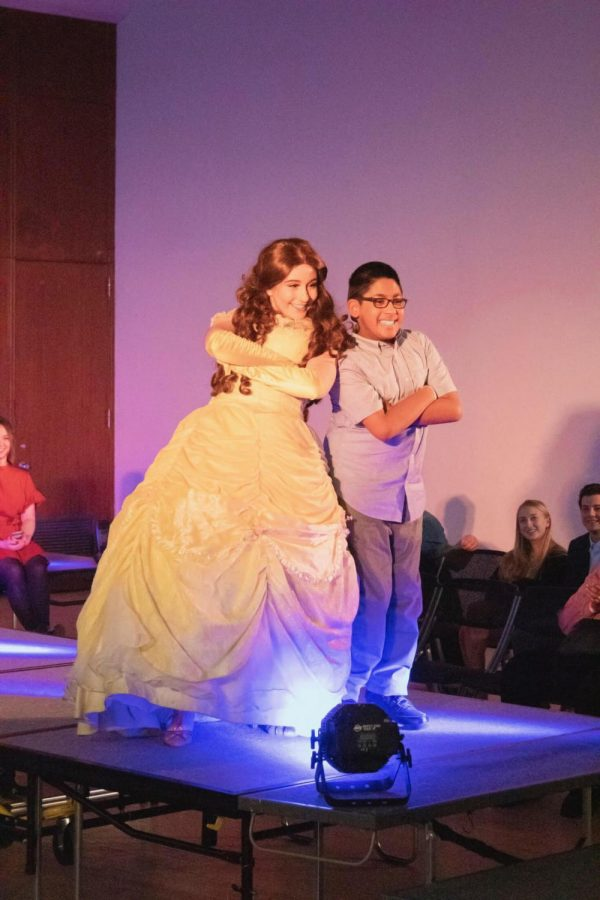 Belle from Moment of Magic walks the runway with one of the Special Olympians. (Joe Byrnes/ The Fordham Ram)