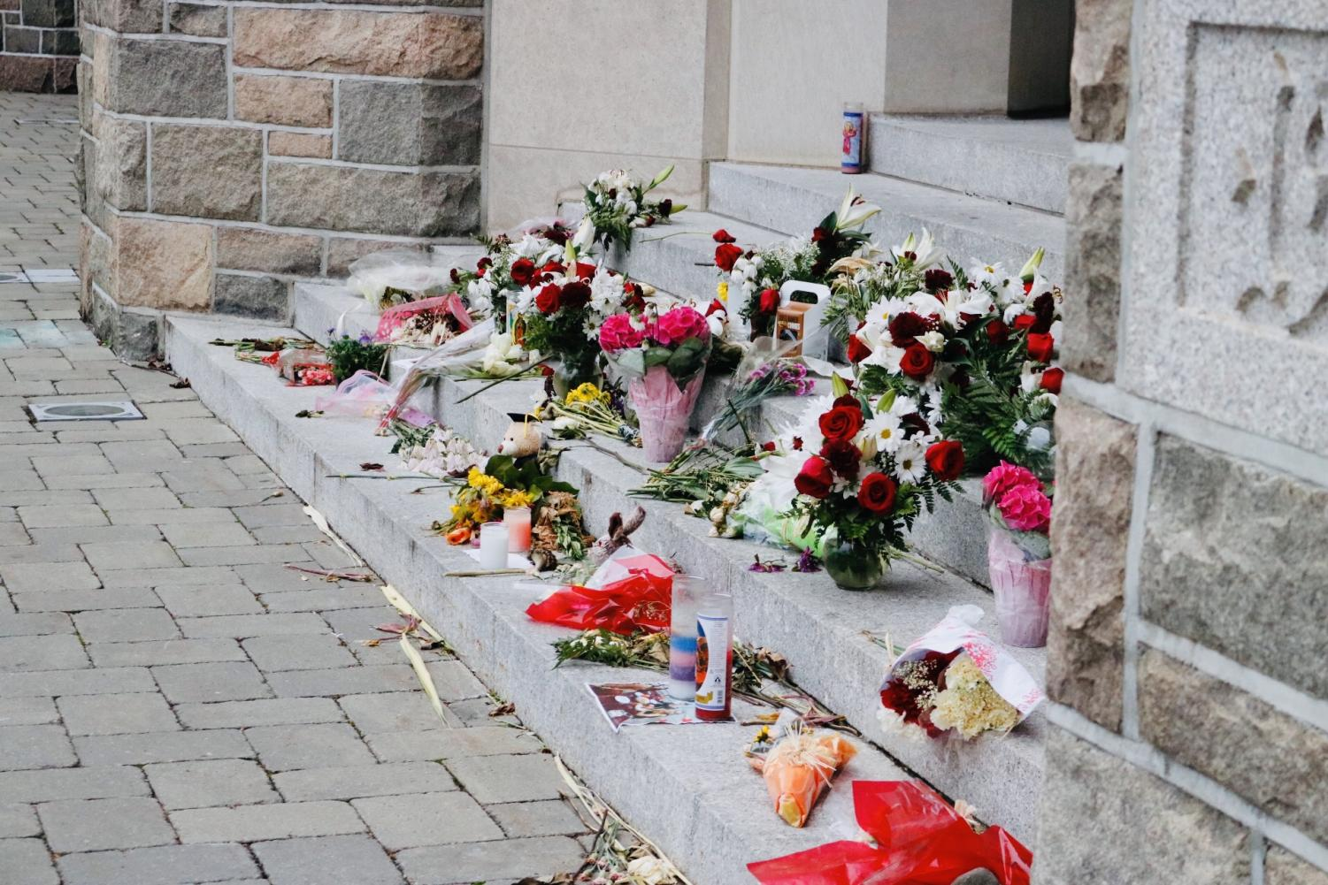 Students placed flowers and candles on the steps of Keating Hall to honor Sydney Monfries. (Julia Comerford/ The Fordham Ram)