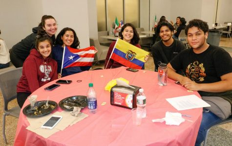 Students enjoy food and hold flage at El Grito's Rep Your Heritage event.
